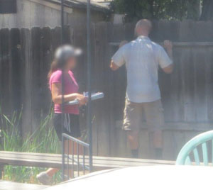 A pair of suspected unlicensed contractors check a fence before submitting a bid at CSLB's Sacramento sting operation.